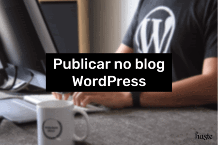 Texto: publicar no blog WordPress. Imagem: pessoa mexendo em um computador e usando uma camisa com o logo do WordPress. Foto ilustrativa e sem detalhes.