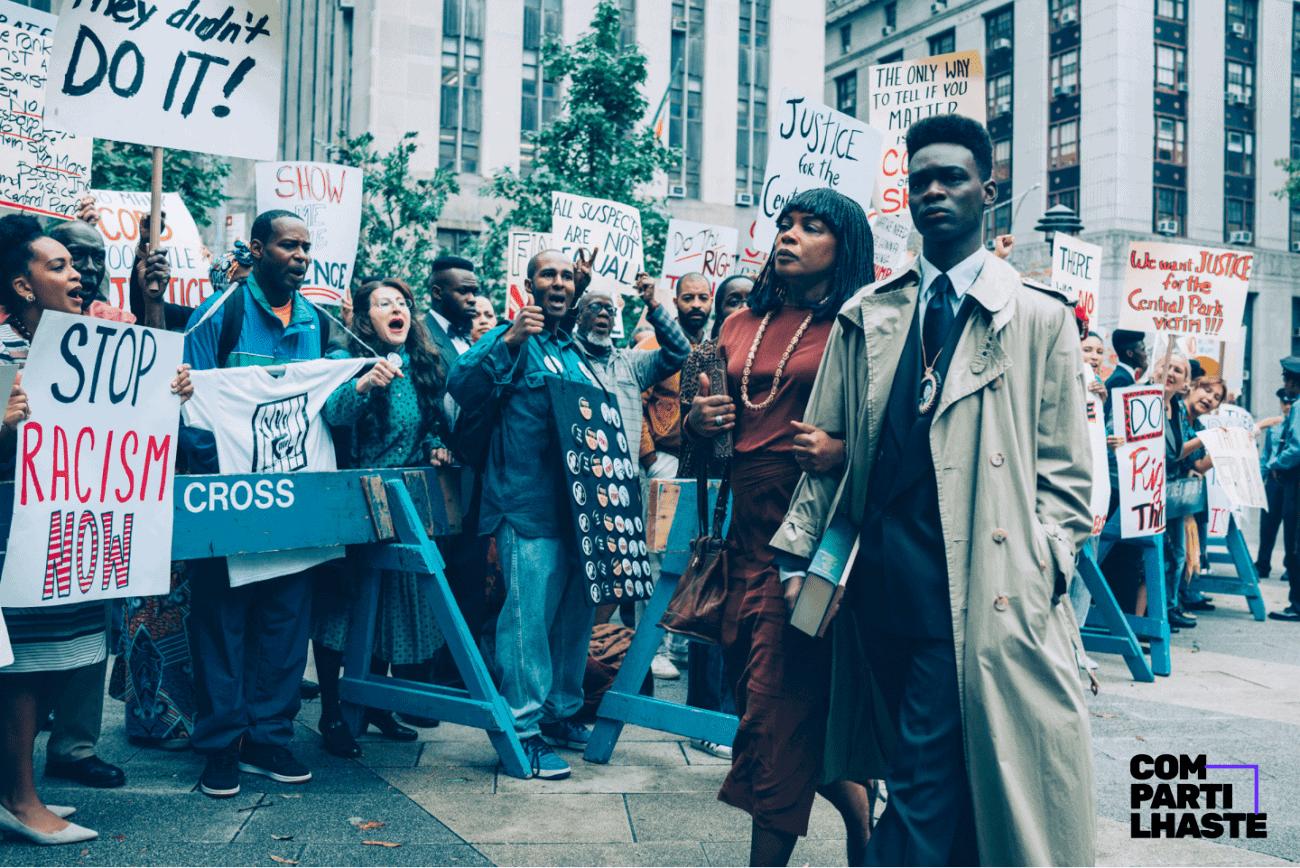 Foto de uma cena da série Olhos que condenam, em que um jovem negro está andando ao lado da mãe enquanto acontece um protesto contra o racismo ao lado.